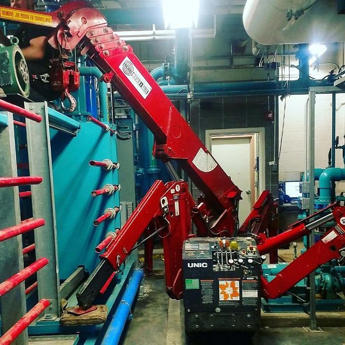 A mini crane spydercrane lifting in a tight spot. Specialty Services.