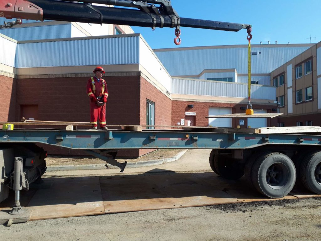 Picker Truck lifting a road plate with a magnet