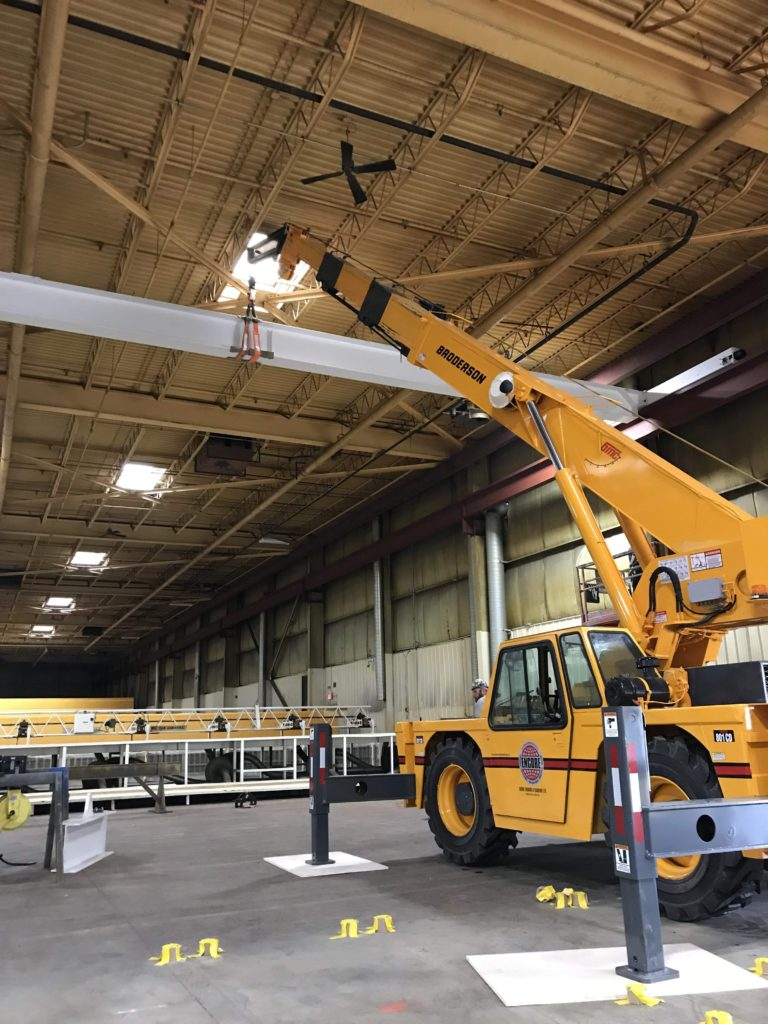 Carry Deck crane lifting in a tight spot in a shop. Specialty Services.